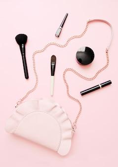 Endecha plana de accesorios de moda femenina, productos de maquillaje y bolso sobre fondo de color pastel