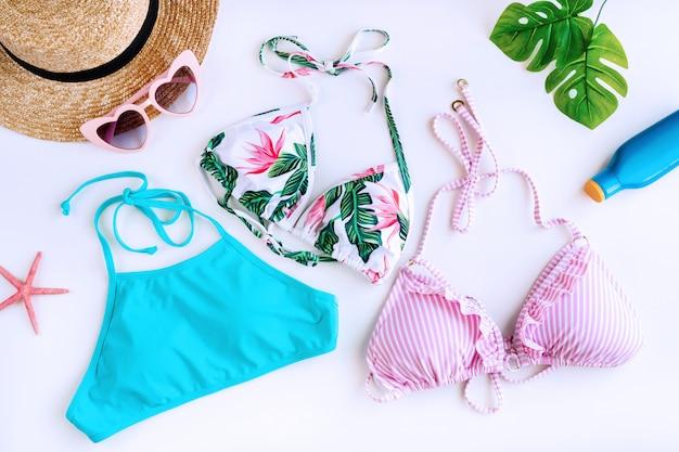 Endecha plana de accesorios de verano con 3 coloridos bikini, protector solar, gorro de playa, coral en forma de estrella de mar, gafas de sol en forma de corazón y hojas de palma aisladas sobre fondo blanco.