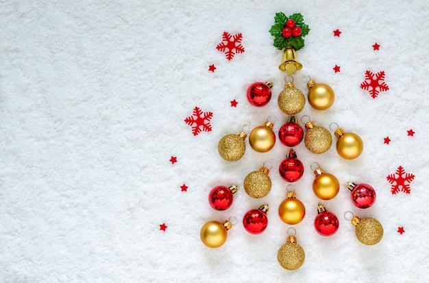 Endecha plana de adornos navideños colocados como un pino sobre nieve