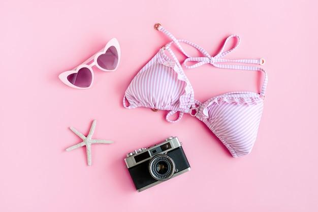 Endecha plana de artículo de verano con bikini de color rosa pastel, gafas de sol, coral en forma de estrella de mar y cámara sobre fondo rosa, vista superior. concepto de verano.