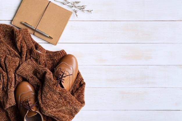 Endecha plana con atuendo cálido y cómodo para clima frío cómodo otoño, compras de ropa de invierno, venta, estilo en concepto de colores de tono tierra, vista superior, espacio de copia