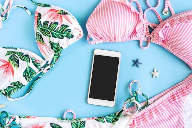 Endecha plana de bikini colorido, teléfono inteligente y gafas de sol en forma de corazón en azul