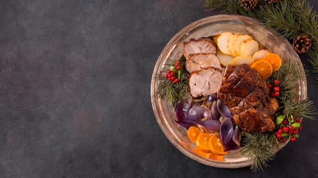 Endecha plana de bistec de navidad en un plato con decoración de piñas y espacio de copia
