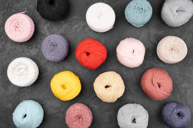 Endecha plana de bolas de lana sobre fondo de pizarra