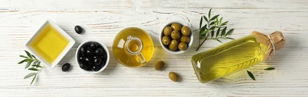 Endecha plana con botella, jarra, tazón con aceite de oliva y aceitunas en madera, espacio para texto
