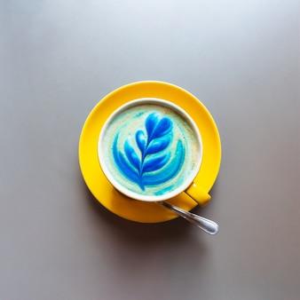 Endecha plana de café con leche azul de moda con pétalos de flores de arte en la espuma