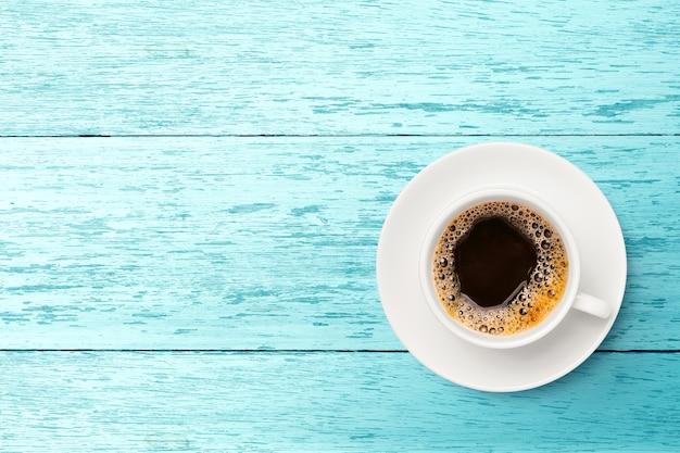 Endecha plana de café negro en taza blanca sobre madera azul claro.