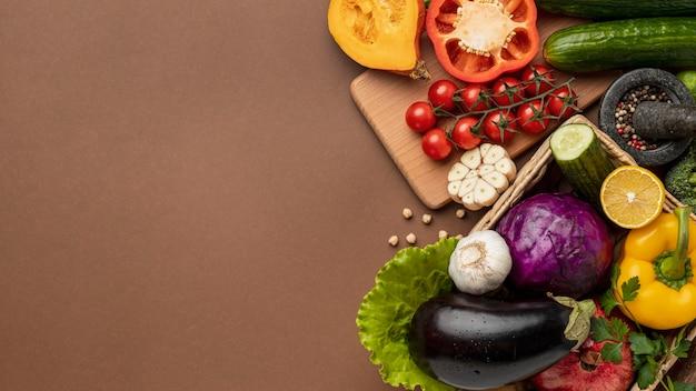 Endecha plana de cesta de verduras orgánicas con espacio de copia