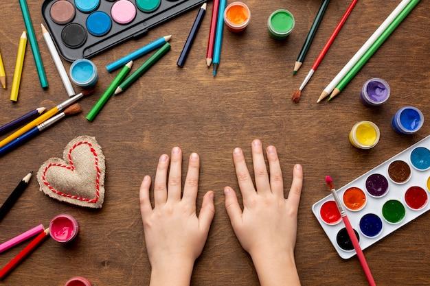 Endecha plana de coloridas acuarelas y manos
