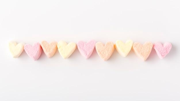 Endecha plana de coloridos hilos de caramelo en forma de corazón