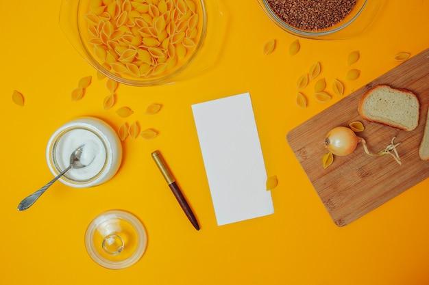 Endecha plana con comida y sábana blanca para texto. trigo sarraceno, productos de macarrones, azúcar, pan y cebolla en la tabla de cortar de madera. escritura de recetas.