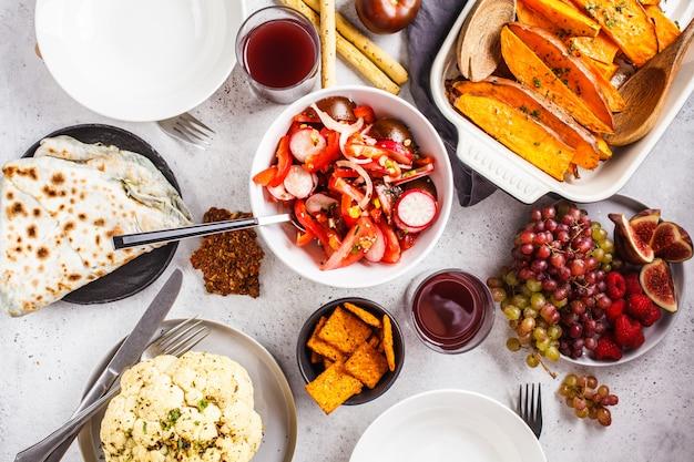 Endecha plana de comida vegana: batata al horno, coliflor, frutas, ensalada de verduras y tortilla con verduras sobre fondo blanco.