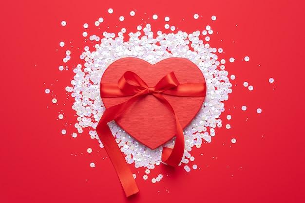 Endecha plana de confeti en forma de corazón de color rosa pastel sobre fondo rojo. concepto de amor celebración navideña día de san valentín. decoración de fiesta de bodas.