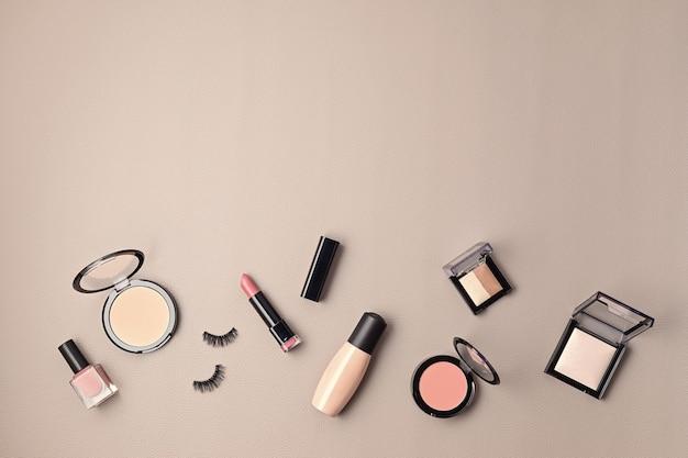 Endecha plana con un conjunto de cosméticos decorativos profesionales, herramientas de maquillaje y accesorios de mujer sobre una pared gris con espacio de copia. blog de belleza, moda, fiesta y concepto de compras. vista superior