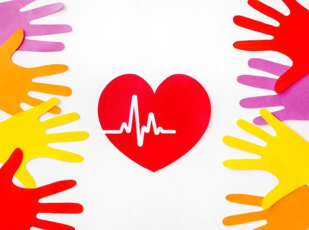 Endecha plana de corazón de papel con latidos del corazón y manos