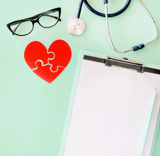 Endecha plana de corazón de papel de rompecabezas con estetoscopio y bloc de notas