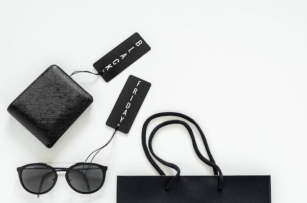 Endecha plana de cosas de hombres: billetera negra, gafas de sol, etiquetas de precio y bolsa de compras sobre fondo blanco para el concepto de venta del viernes negro