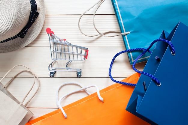 Endecha plana creativa de concepto de compras con carro de compras y multicolor de bolsas de compras