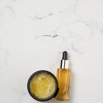 Endecha plana de crema y botella de aceite esencial sobre fondo de mármol