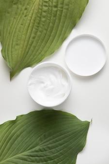 Endecha plana de crema y hojas sobre fondo blanco.