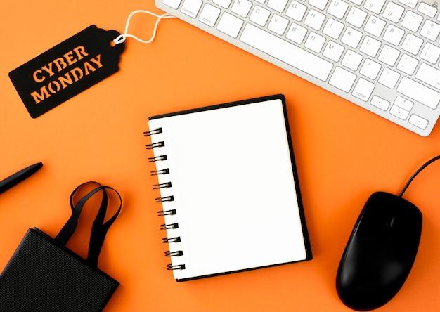 Endecha plana de cuaderno con bolsa de compras y etiqueta de cyber monday en el teclado