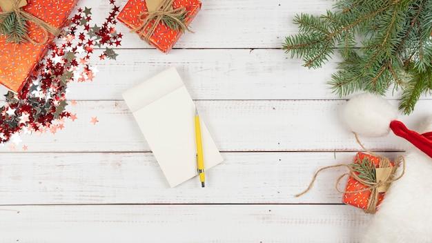 Endecha plana de cuaderno sobre fondo de madera, decoración navideña alrededor