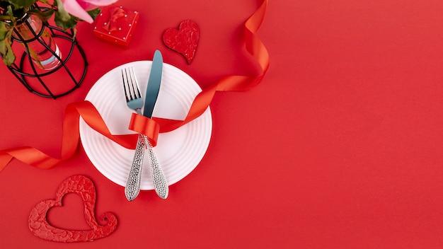 Endecha plana de cubiertos en plato con cinta y corazones