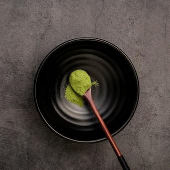 Endecha plana de cuchara de madera en un tazón con polvo de té matcha