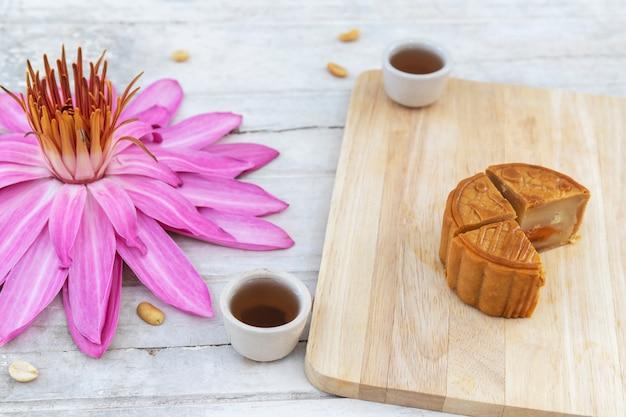 Endecha plana de festival de mediados de otoño torta de luna en la vieja mesa blanca con lirio de agua rosa y tés