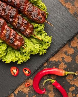 Endecha plana de delicioso kebab en pizarra con ensalada