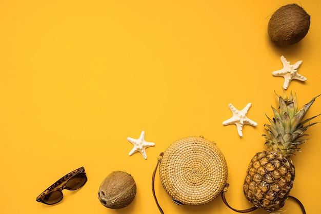 Endecha plana del equipo femenino de la moda del verano colorido. bolsa de bambú, gafas de sol, coco, piña y estrellas de mar sobre fondo amarillo, vista superior