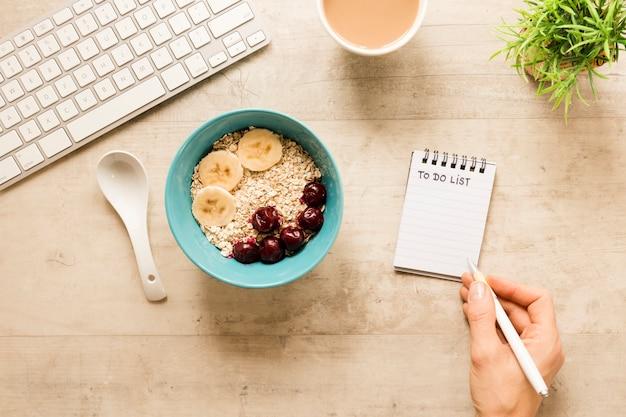 Endecha plana y escribiendo en el cuaderno cerca del tazón con avena y frutas