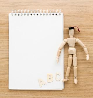 Endecha plana de figurilla de madera con gorro académico y cuaderno