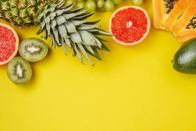 Endecha plana de frutas tropicales sobre fondo amarillo. nutrición veraniega, alimentación saludable.
