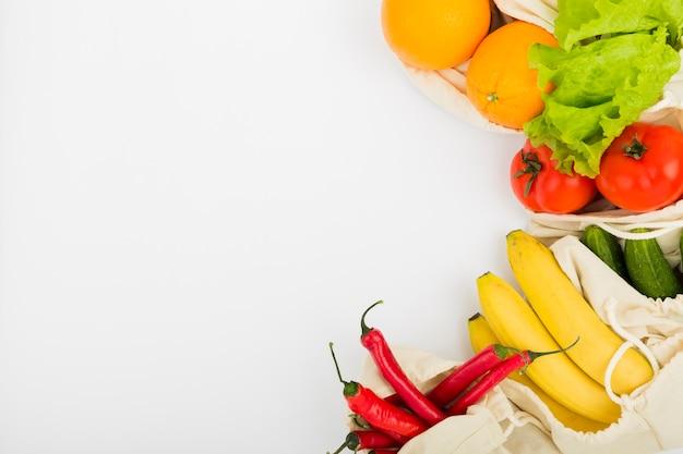 Endecha plana de frutas y verduras en bolsas reutilizables con espacio de copia