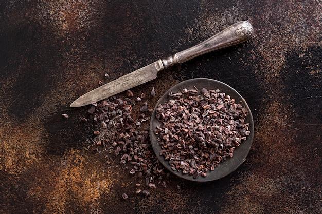 Endecha plana de granos de cacao molidos en un plato con cuchillo