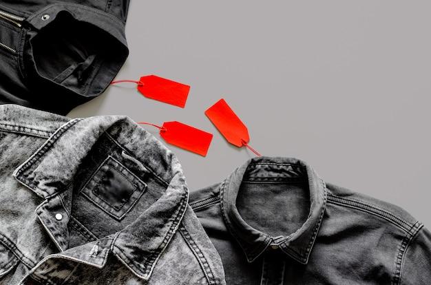 Endecha plana de hombres ropa negra con etiquetas de precios rojas sobre fondo gris para el concepto de venta de compras de black friday.
