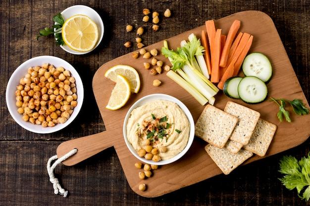 Endecha plana de hummus con variedad de verduras.