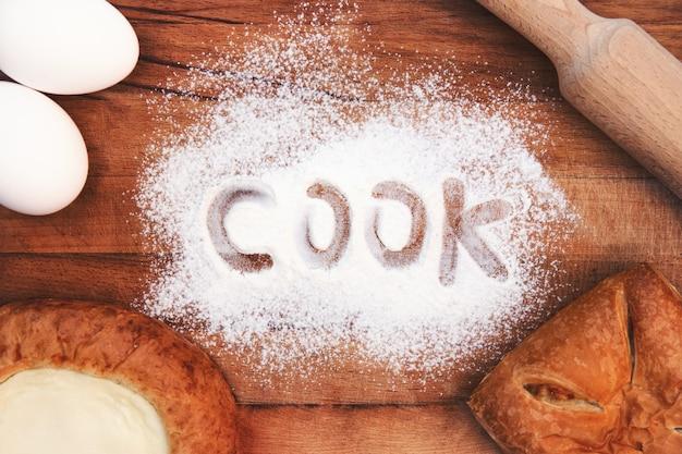 Endecha plana. ingredientes para hornear sobre un fondo de madera. utensilios de cocina, rodillo, huevos, harina, tarta de queso y tarta. cocine escrito en harina.
