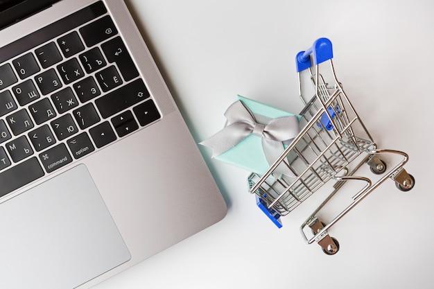 Endecha plana con laptop, carrito de supermercado y caja de regalo