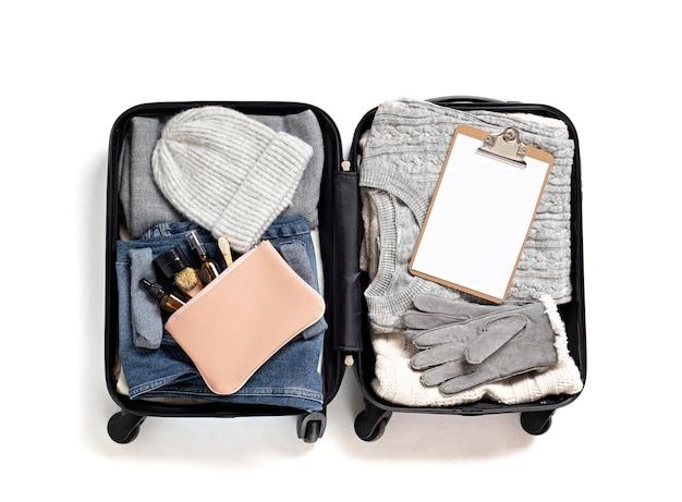Endecha plana con maleta abierta con ropa casual para otoño, vacaciones de invierno sobre pared blanca. vacaciones de invierno, viajes, turismo, concepto de equipaje de vuelo. vista superior