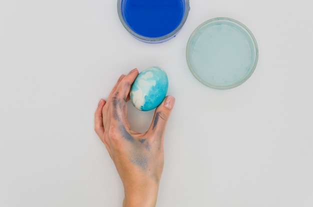 Endecha plana de mano sosteniendo huevo de pascua teñido