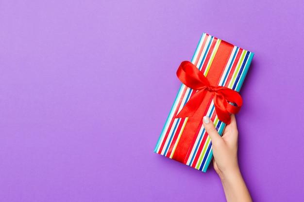 Endecha plana de manos de mujer sosteniendo regalo envuelto y decorado con arco sobre fondo morado con espacio de copia. concepto de navidad y vacaciones