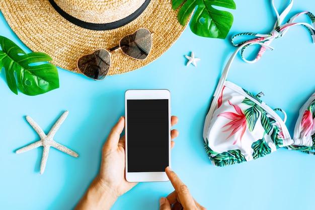 Endecha plana de manos de mujer usando un teléfono celular y un artículo de verano con bikini colorido, sombrero de paja, coral, gafas de sol en forma de corazón y hojas de palma, vista superior
