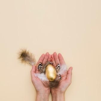 Endecha plana de manos sosteniendo el huevo de pascua dorado con plumas y espacio de copia