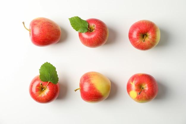 Endecha plana con manzanas rojas en mesa blanca