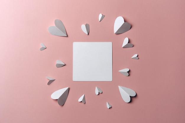 Endecha plana de maqueta en blanco en blanco con corazones de papel alrededor sobre fondo rosa.