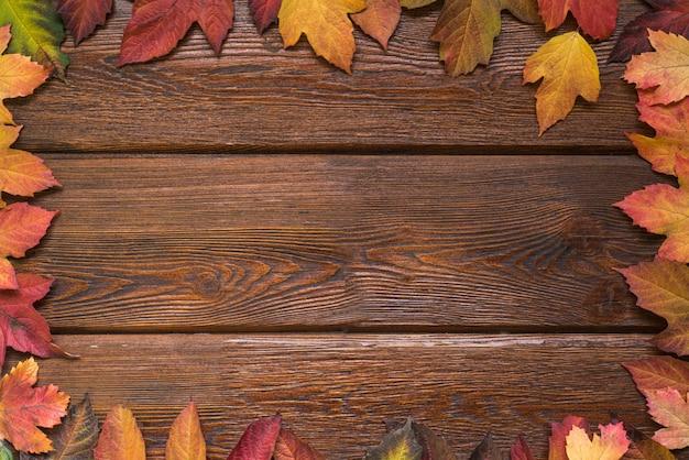 Endecha plana con marco de borde de hojas de otoño sobre fondo de madera oscura rústica.