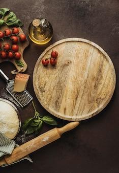 Endecha plana de masa de pizza con tablero de madera y tomates