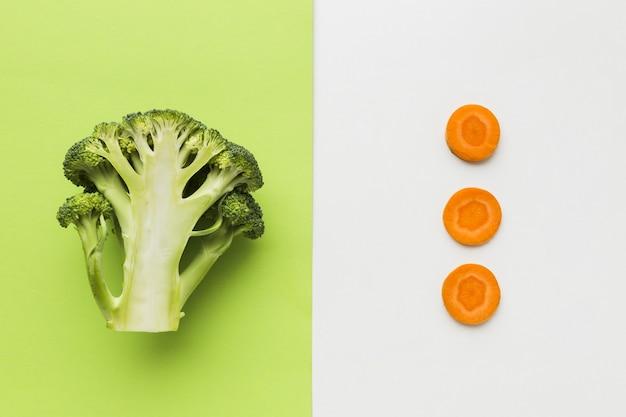 Endecha plana de medio rodajas de brócoli y zanahoria